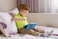 Caucasian toddler boy sitting in bed playing with digital tablet with funny face expression. Portrait of cute adorable white Caucasian toddler boy sitting in bed royalty free stock image