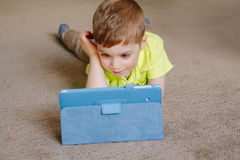Caucasian toddler boy sitting in bed playing with digital tablet with funny face expression. Portrait of cute adorable white Caucasian toddler boy lying on floor royalty free stock photos