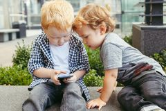 Caucasian toddlers boys sitting together and playing games on cell mobile phone digital tablet royalty free stock photography