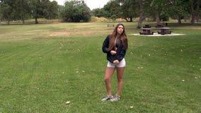 Caucasian tonårig flicka i vita kortslutningar och svart omslag med hoodien lager videofilmer