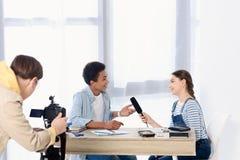 caucasian tonårig unge som för intervju med afrikansk amerikanvännen arkivfoton