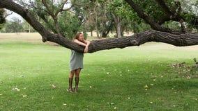 Caucasian tonårigt flickaanseende som under ser över trädfilial och flyttning lager videofilmer