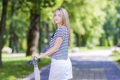 Caucasian tonårs- flicka som poserar med den långa skateboarden i grön skog Arkivfoton