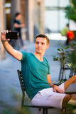 Caucasian tourist with smartphone taking selfie sitting in outdoor cafe. Young urban boy on vacation exploring european Royalty Free Stock Image