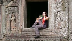 caucasian tourist talking with mobile phone in angkor stock footage