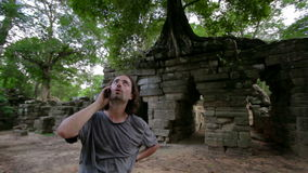 Caucasian tourist talking with mobile phone, ruins in tropical jungle Royalty Free Stock Photography