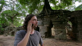 Caucasian tourist talking with mobile phone, ruins in tropical jungle Royalty Free Stock Image
