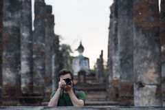 Caucasian traveler making photo while traveling at buddhism temple in Thailand. Photos for memories Stock Images