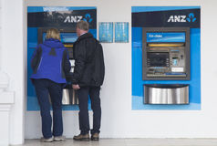 Caucasian travelers making transaction at an automatic teller machine ATM of ANZ Royalty Free Stock Photos