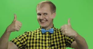Caucasian trendiga manshowtummar upp Grabb i gul skjorta Tv? i en: 1 lager videofilmer
