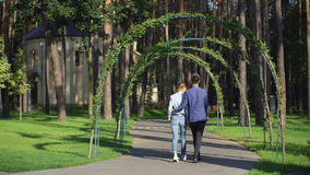 Caucasian two persons wearing in casual dress like fashionable denim shirt and blue stylish jacket. Man and woman walking in the city park with pine trees stock video