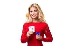 Caucasian ung kvinna med långt ljust blont hår i aftondräktinnehavet som spelar kort och chiper isolerat poker Royaltyfria Bilder