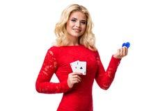 Caucasian ung kvinna med långt ljust blont hår i aftondräktinnehavet som spelar kort och chiper isolerat poker Royaltyfri Fotografi