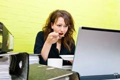 Caucasian ung kvinna som äter och arbetar på hennes bärbar datordator på hennes skrivbord arkivbilder