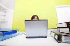 Caucasian ung kvinna som arbetar på hennes bärbar datordator på hennes skrivbord Fotografering för Bildbyråer