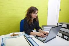 Caucasian ung kvinna som arbetar på hennes bärbar datordator på hennes skrivbord arkivfoton