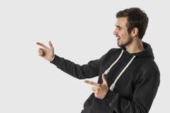 Caucasian ung man som pekar temptingly på tomt utrymme bakgrund isolerad white Annonseringbegrepp arkivfoton