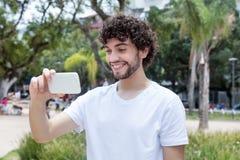 Caucasian ung vuxen man med hållande ögonen på tv för skägg med telefonen royaltyfria foton