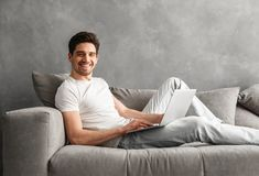 Caucasian unshaved man 30s in casual clothing using notebook, wh. Caucasian unshaved man 30s in casual clothing using notebook while lying on cozy sofa in gray Royalty Free Stock Photos