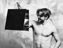 Caucasian uppsökt sexig macho man som rymmer den röda packen eller påsen Fotografering för Bildbyråer