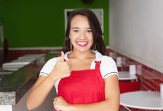 Caucasian waitress in a fast food restaurant showing thumb Stock Photo