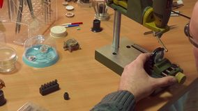 Watchmaker uses drill press. Caucasian watchmaker using drill press at his work. Hairless male repairer lowering drill head. Middle aged man winding the feed Stock Images