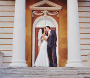 Caucasian wedding couple standing on steps of an old building. Royalty Free Stock Photos