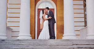 Caucasian wedding couple standing on steps of an old building. Royalty Free Stock Photo