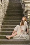 Caucasian white female model and brick stone. Beautiful girl, long red hair, beige skirt and cardigan. Woman siting on the stairs Stock Images
