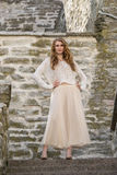 Caucasian white female model and brick stone. Beautiful girl, long red hair, beige skirt and cardigan. Woman standing on the stair Stock Photo