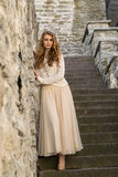 Caucasian white female model and brick stone. Beautiful girl, long red hair, beige skirt and cardigan. Woman standing on the stair Stock Photography