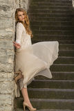 Caucasian white female model and brick stone. Beautiful girl, long red hair, beige skirt and cardigan. Woman standing on the stair Stock Photos