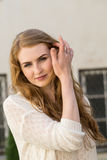 Caucasian white female model portrait and house in the background. Beautiful girl, long red hair, beige skirt and cardigan Royalty Free Stock Images