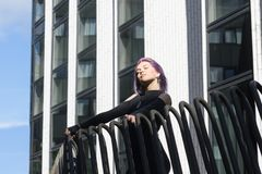 Caucasian white female model standing on the balcony of the building and enjoys weather. Beautiful woman with long purple hair. In a gray dress resting in the Royalty Free Stock Photo