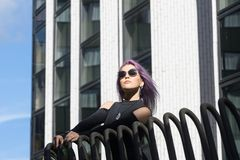 Caucasian white female model standing on the balcony of the building and enjoys weather. Beautiful woman with long purple hair. In a gray dress resting in the Stock Photos