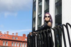 Caucasian white female model standing on the balcony of the building and enjoys weather. Beautiful woman with long purple hair. In a gray dress resting in the Stock Photography