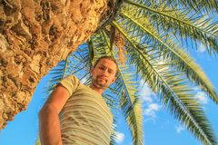 Caucasian white male traveler with long hair and beard stands next to palm tree royalty free stock photos