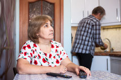 Caucasian wife watches TV and rests, husband helps in the kitchen - washes dishes Royalty Free Stock Photos