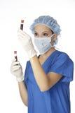 Beautiful woman laboratory technician examining a tube of blood Stock Photo