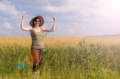 Young woman with hat enjoying the nature. Victory concept. Caucasian woman with arms raised celebrating her success in a field on a summer day Royalty Free Stock Images