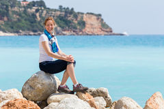 Caucasian woman as tourist sitting on rocks near sea Stock Photo