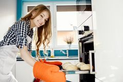 Caucasian woman baking a bread in kitchen oven. She pulls rolls from the oven. Hands protected by orange kitchen gloves Stock Photo