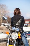 Woman in black leather jacket turn back upon while sitting on motorcycle Royalty Free Stock Images