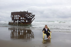 Caucasian Woman in Business Suit Sitting at Shipwreck Royalty Free Stock Images