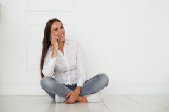 Caucasian woman in cheerful pensive mood is talking on smart phone Royalty Free Stock Image