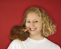Caucasian woman with chicken on shoulder. Stock Photos
