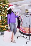 Caucasian woman choosing dresses for Christmas gift. Portrait of Caucasian woman choosing a dress for Christmas gift and standing in the mall Royalty Free Stock Photos