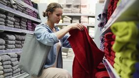 Caucasian woman choosing towels from big variety in the row. Shelves in store are fulled of different towels of any. Color. Girl unfolds one big red towel from stock footage