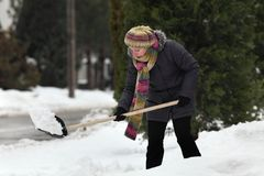 Winter time, snow removing from street. Caucasian woman cleaning snow from sidewalk using shovel, winter time Stock Images