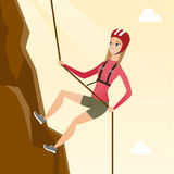 Caucasian woman climbing a mountain with rope. Young climber in protective helmet climbing a mountain. Caucasian smiling woman climbing a mountain with a rope Stock Image